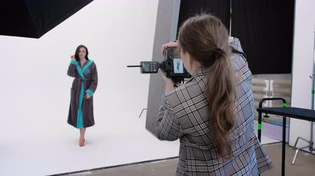 elfog : Back view of woman using photo camera to shoot female model in pink bathrobe during photoshoot in professional studio Stock mozgókép