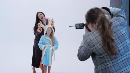 захват : Back view of lady with photo camera taking pictures of cheerful mother and daughter in bathrobes against gray background Стоковые видеозаписи