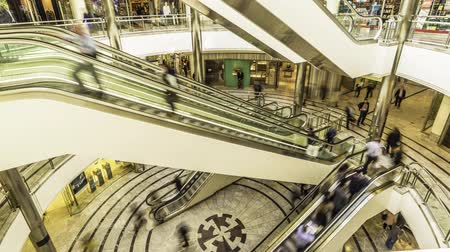 docklands : Time lapse of escalators with people rushing through in a shopping centre in Canary Warf London Stock Footage