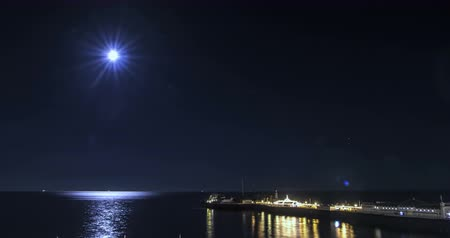 полный : Time lapse view of a full moon night on the beach in Brighton