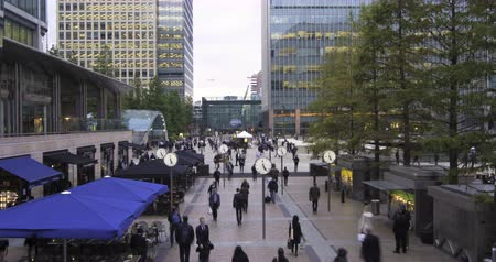 docklands : Time lapse view of people rushing from work with several clocks in the Docklands, financial centre in London