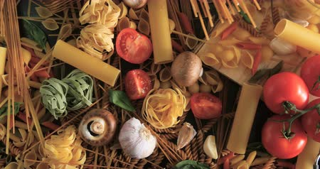 massa : Dolly tilt down view of different variety of Italian pasta and ingredients