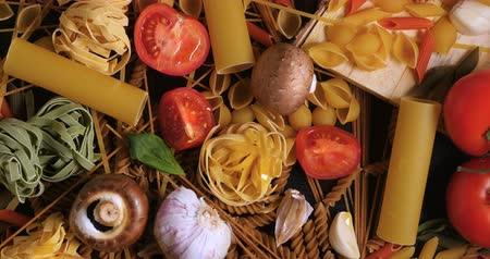 rajčata : Dolly tilt down view of different variety of Italian pasta and ingredients
