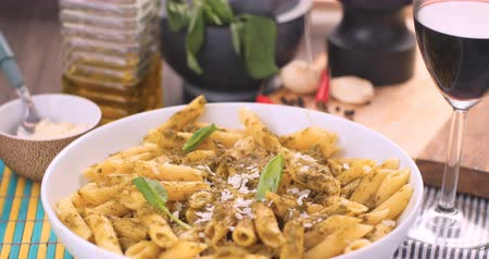 parmigiano : Grating parmesan cheese over Italian pasta (penne) with pesto sauce