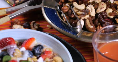 cereais : Dolly push out view of a breakfast of cereals with berries, dry fruits, milk and whipped cream