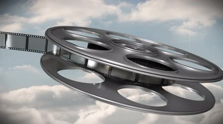 taŚma filmowa : Digitally generated of film reel against sky background