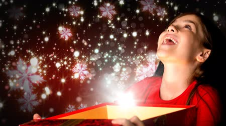 Навидад : Digital composite of Excited girl opening magical Christmas gift box with sparkling snowflakes Стоковые видеозаписи