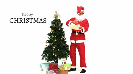 Санта : Digital composite of Happy Christmas text and Santa next to Christmas tree Стоковые видеозаписи