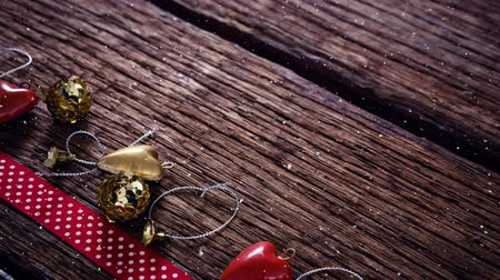 golden ribbon : Digital composite of Falling snow with Christmas decoration on wood Stock Footage