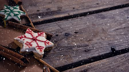 indulgência : Digital composite of Falling snow with Christmas decorations on wood Stock Footage