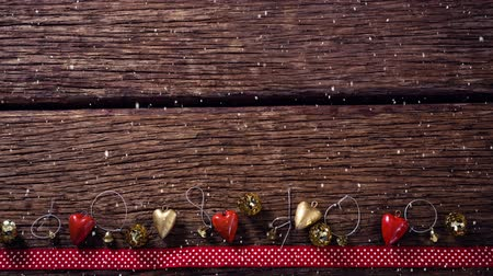 святки : Digital composite of Falling snow with Christmas decorations on wood Стоковые видеозаписи