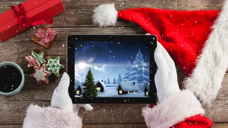 gorro papa noel : Compuesto digital de composición de video con nieve sobre la vista superior de santa con tableta Archivo de Video