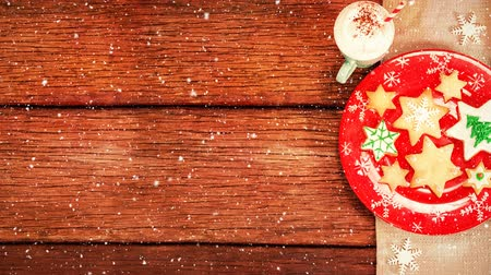 ivászat : Digital composite of Christmas cookies and hot drink on wood combined with falling snow