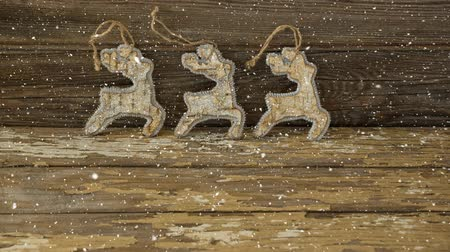 устроенный : Digital composite of Falling snow with Christmas reindeer decoration on wood Стоковые видеозаписи