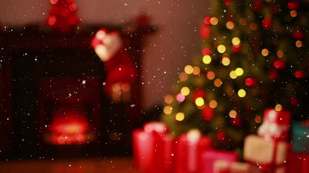 şömine : Digital composite of Video composition with falling snow over blurry video of Christmas tree lights and presents in cozy room Stok Video