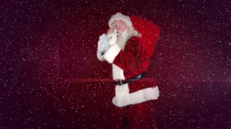 to celebrate : Digital composite of Video composition with falling snow over  santa walking with sack on his back