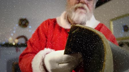 ev gibi : Digital composite of Video composition with falling snow over slow motion santa flipping through book