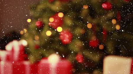 С Рождеством : Digital composite of Video composition with falling snow over blurry video of Christmas tree lights and candles