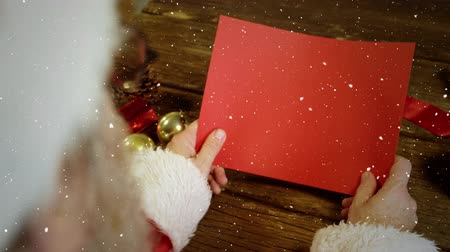 顔写真 : Digital composite of Video composition with falling snow over desk with santa holding red card