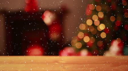 определение : Digital composite of Video composition with falling snow over blurry video of Christmas tree lights and desk in front