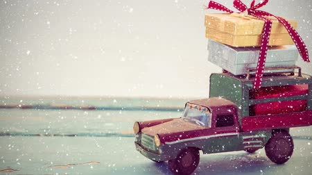 wrapped up : Digital composite of Model car with christmas presents on its roof combined with falling snow