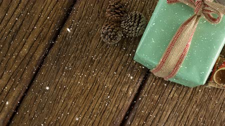 envolto : Digital composite of Falling snow with Christmas gift decoration on wood