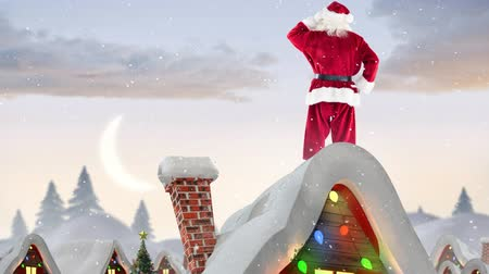 hilâl : Digital composite of Santa clause on a roof of a decorated house in winter scenery combined with falling snow
