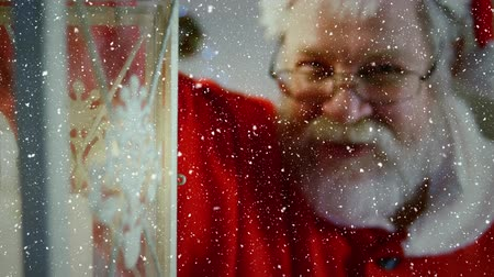 ev gibi : Digital composite of Video composition with falling snow over santa holding lattern