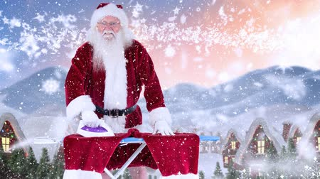 ütüleme : Digital composite of Santa clause ironing his trousers combined with falling snow