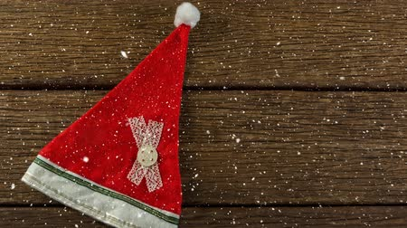 headwear : Digital composite of Falling snow with Christmas Santa hat on wood Stock Footage