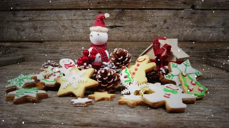 kar taneleri : Digital composite of Video composition with falling snow over desk with ginger cookies and santa doll