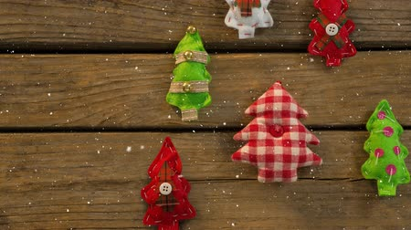 checked pattern : Digital composite of Falling snow with Christmas tree decorations on wood