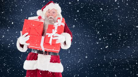 святки : Digital composite of Santa clause holding christmas presents combined with falling snow Стоковые видеозаписи