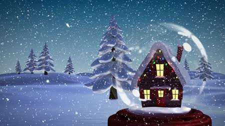 zimní : Christmas animation of illuminated hut. Snow falling over the snow covered landscape, trees 4k