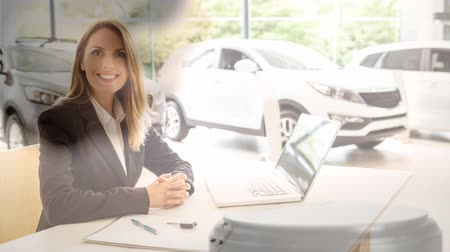 veredito : Digital animation of Smiling sales executive working in the showroom. Cars kept in display at background 4k Vídeos