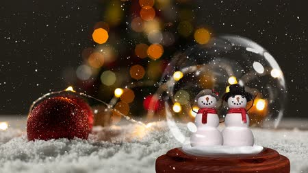 kardan adam : Cute Christmas animation of snowman couple in snow globe. Snow is falling over bokeh background 4k