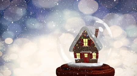 počítačová grafika : Christmas animation of hut in snow globe. Snow falling against bokeh background 4k