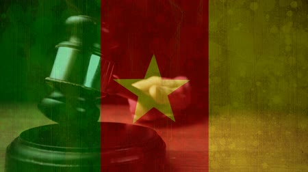 adli : Digitally composite of grunge Cameroon Flag and gavel. Judges gavel banging against the flag 4k