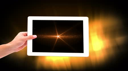 brilho : Digital animation of woman holding digital tablet showing illuminated lights. Glowing lights in background 4k Vídeos