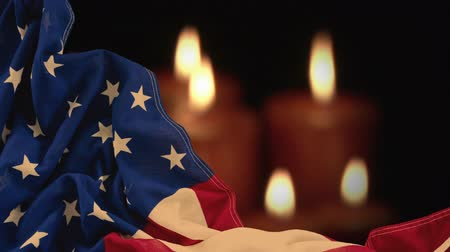 освещенный : Digital animation of crumpled American flag against lit candles. Lit candles glowing in dark 4k