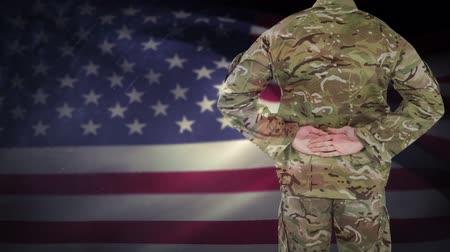 komutan : Digital animation of proud american soldier standing in front of the American Flag. Flag swaying in wind 4K Stok Video