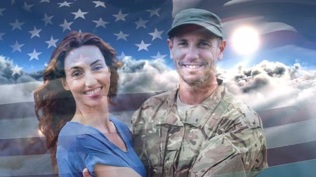 homecoming : Digital animation of American soldier embracing his wife after home returning against American flag. American flag swaying in cloud and sun 4k Stock Footage