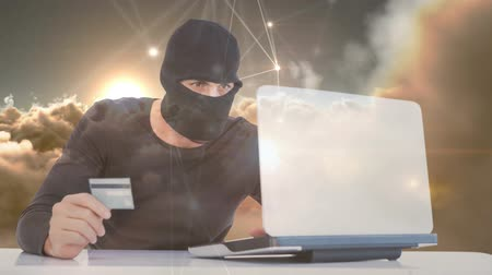 кодирование : Digital animation of hacker holding card while hacking the laptop. White clouds moving in the sky at sunset 4K