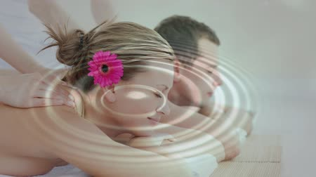 массаж : Digital composite of happy relaxed couple getting a massage together with peaceful video of water dropping in background. Стоковые видеозаписи