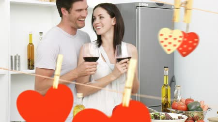 s : Digital composite of happy young couple enjoying each others company and being affectionate in kitchen while drinking wine, with hearth on a clothesline in forefront