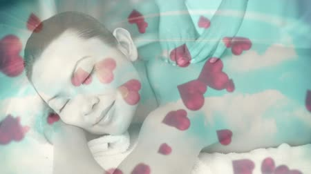 só : Digital composite of relaxed woman enjoying her time getting a massage with animated hearts going up Stock Footage