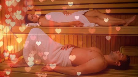 s : Digital composite of couple relaxing together in sauna with digital hearts spreading from the side. Happy couple spending time together Stockvideo