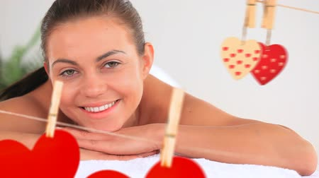 lét : Portrait of a happy smiling beautiful women at spa with red paper hearts hanging for st valentine day Stock mozgókép