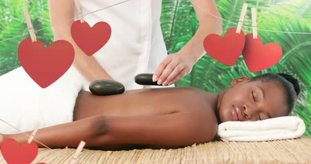 toalha : Masseuse placing hot basalt massage stones on the back of an attractive lying black female at spa for saint valentine day 4k Stock Footage
