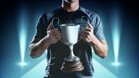 ösztönző : Sports Winner holding trophy on moving digital animated background with lights on the side Stock mozgókép
